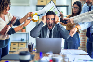 Man stressed at work being pressured by co-workers.