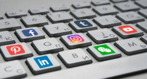 Keyboard keys with different social media logos.