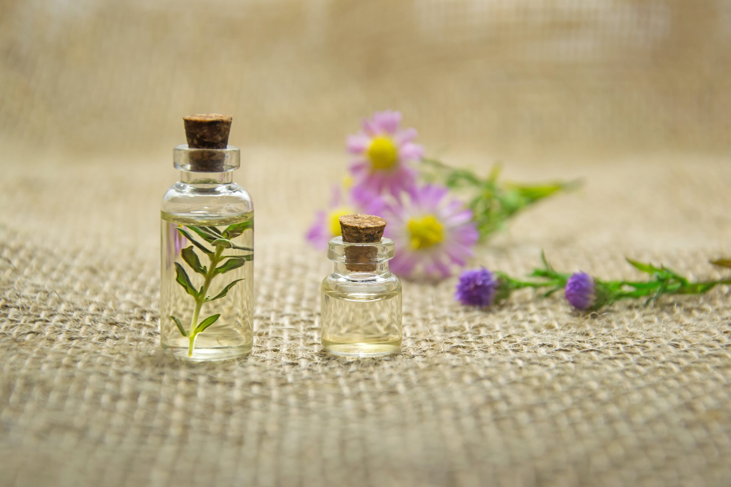 Bottles of essential oil with flowers behind.
