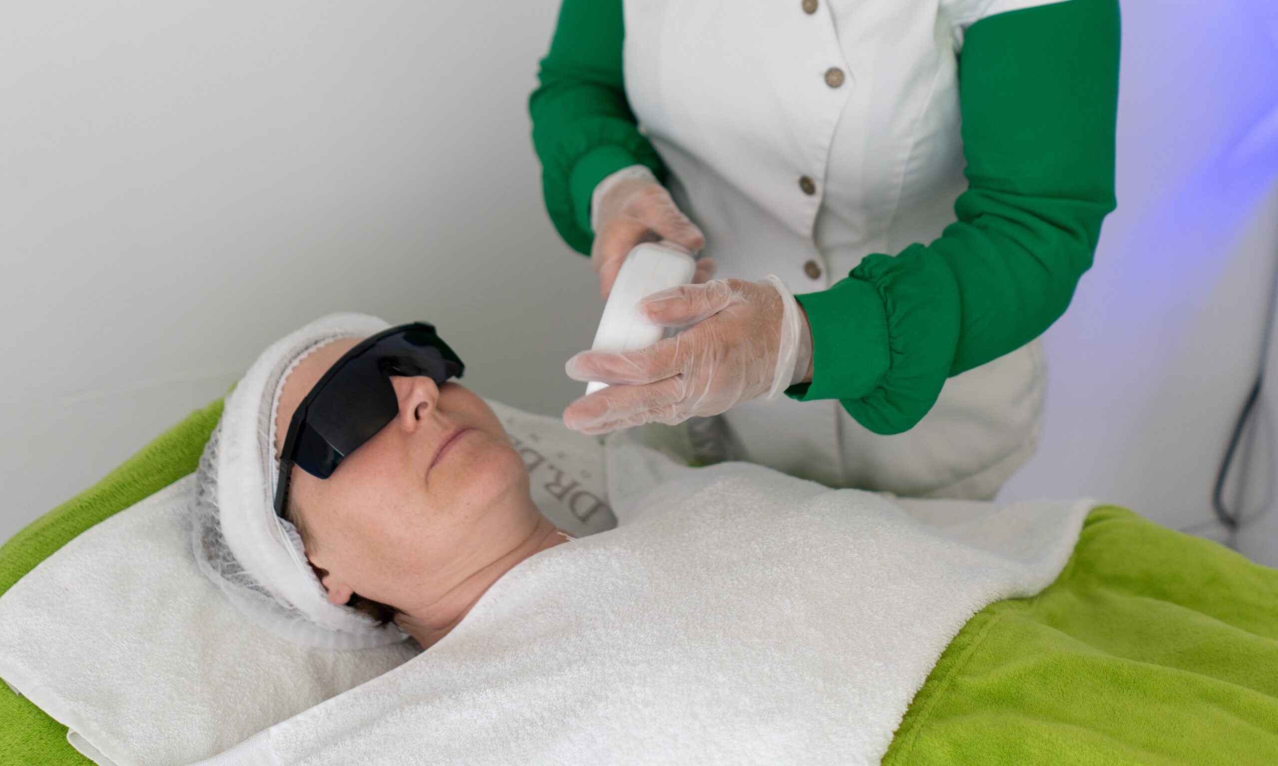 A woman lying with glasses on getting laser hair beauty treatment.